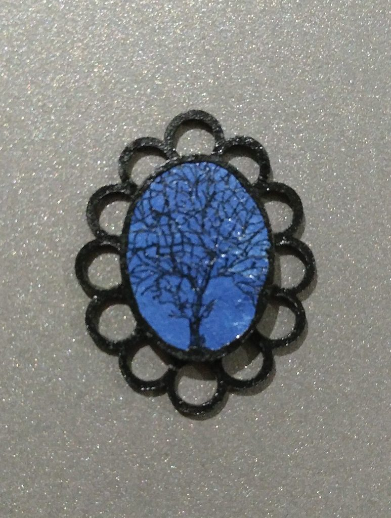 Blue oval jewel with an intricate black tree and a looped black surround,